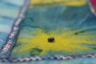 Grünblaue Filzverläufe auf einem Filzteppich